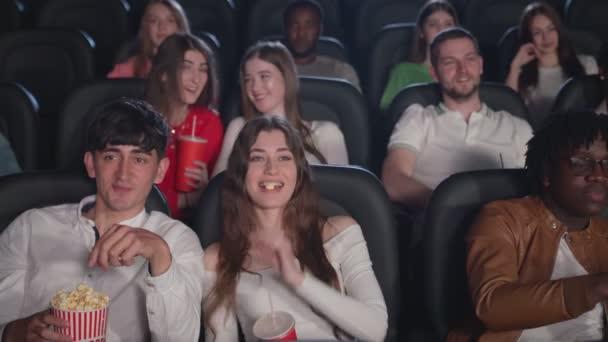 Junge Leute gucken Komödie, essen Popcorn im Kino.