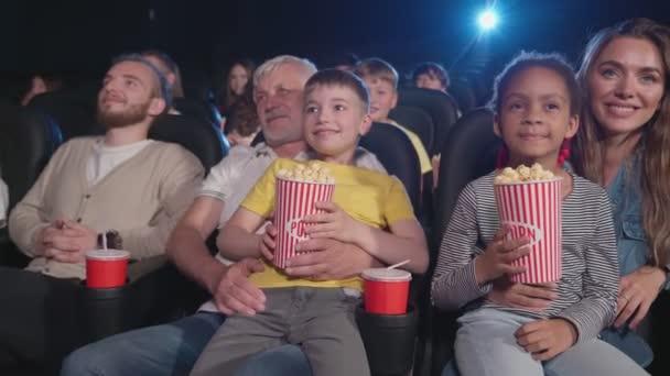 A szülők a gyerekek térdre a moziban.