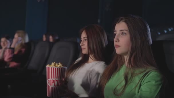 Freundinnen essen Popcorn im Kino.