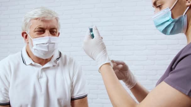 Krankenschwester bereitet Spritze mit Medikamenten für Patientin vor.
