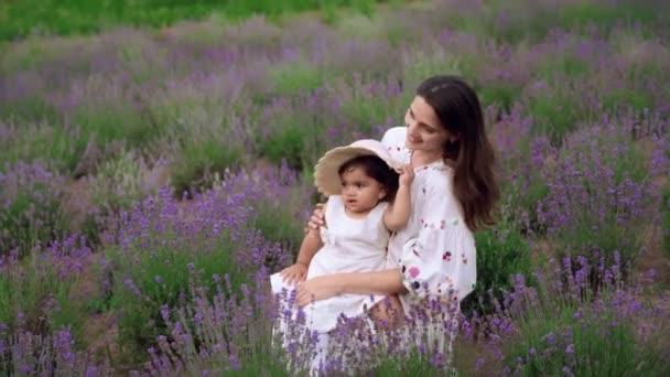 Žena objímání a líbání dítě dcera v levandulovém poli.