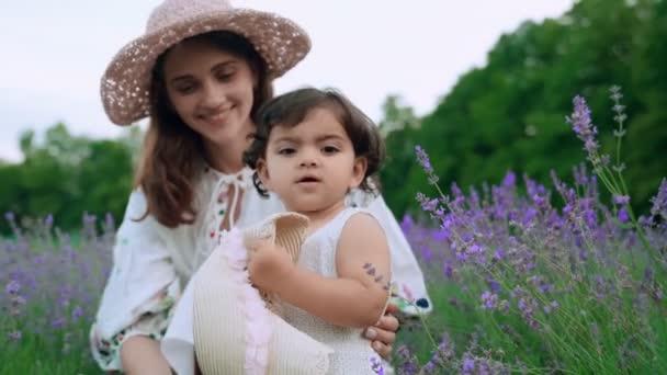 Mutter amüsiert sich mit Baby im Lavendelfeld.