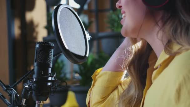 Fiatal aranyos nő énekel mikrofonba.