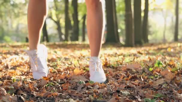 Frau in Turnschuhen streckt Beine im Freien