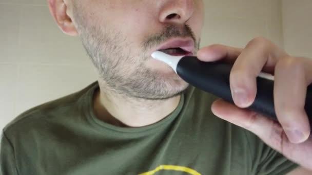 Ein bärtiger Mann putzt sich mit offenem Mund im Spiegel die Zähne. Zahnpasta auf einer elektrischen Zahnbürste