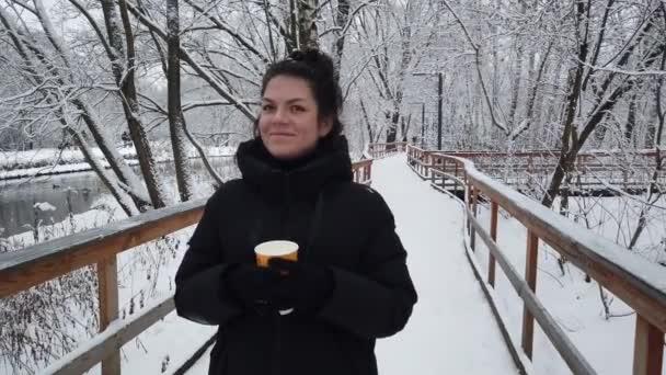 Gyönyörű fiatal lány sétál télen a parkban egy pohár kávéval a kezében.