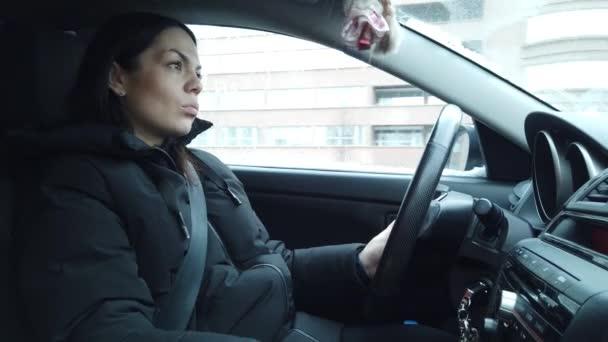 Porträt einer Frau, Seitenansicht. Autofahrerin unterwegs. Junge Frau fährt Auto in der Stadt und hält Hände am Lenkrad.