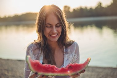 Girl eating watermelon and smiling. Sunset