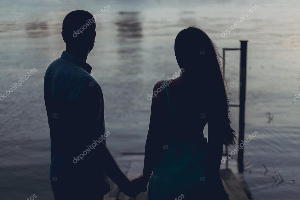 Couple holding hands and looking in the sunset