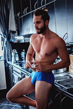 Man in underwear drinking coffee in the kitchen