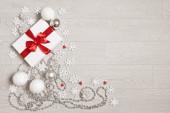 Dárek s červenou mašlí a vločkami. Novoroční dárek. Bílý box s červenou stuhou.