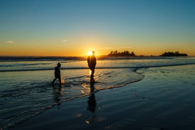 Father and son walking in the surf at Chesterman Beach in Tofino