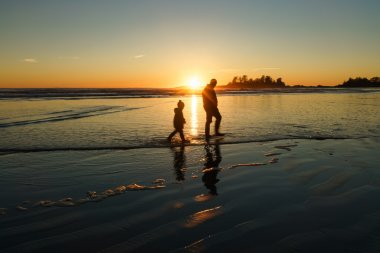Father and son walking in the surf at Chesterman Beach in Tofino, British Columbia
