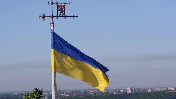Letecký záběr ukrajinské vlajky létání nad nádherné Panorama města Lvov. Zpomalený pohyb 50 fps