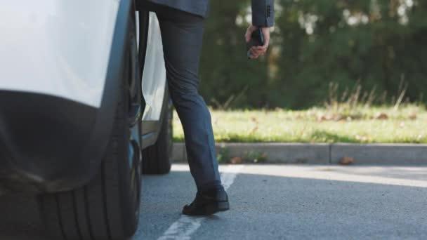 Mann steigt tagsüber in weißes Auto auf Parkplatz Lebensstil in der Stadt. Mit Erfolg. Reichtum