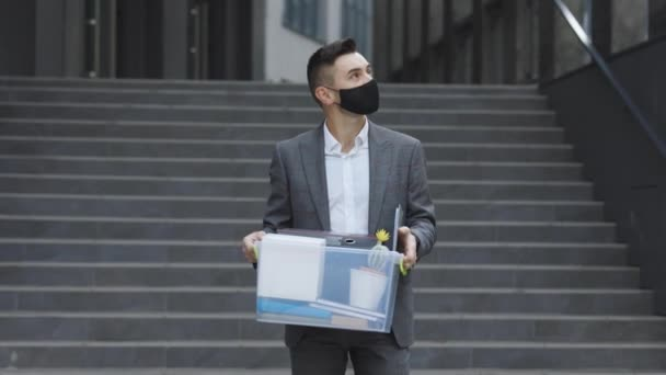 Fired sad young businessman in medical mask carries box with personal belongings leaving the office. Unemployment. Lack of jobs. Financial crisis.