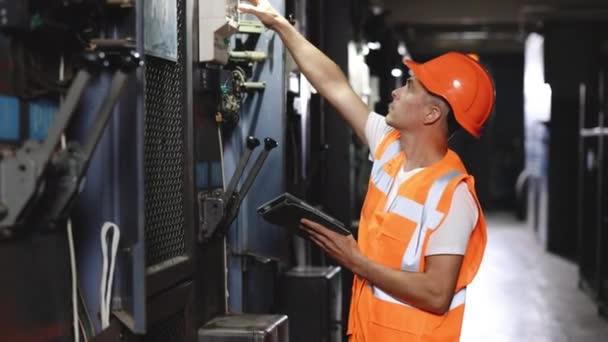 Inženýr používající digitální kontrolu tabletů a kontrolu na panelu MDB. Pracují s elektrickým rozvaděčem na kontrole dosahu napětí v továrně na hlavní rozvaděče.