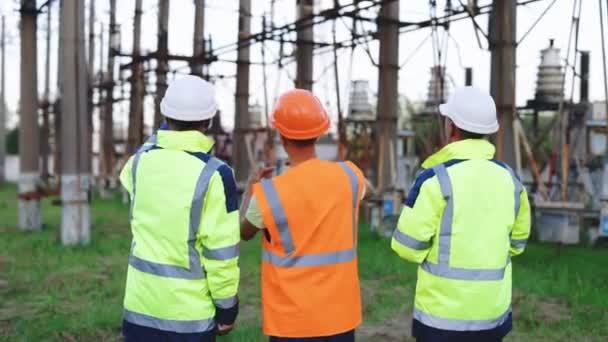 Energetici diskutují o pracovním plánu. Tři inženýři s elektrickými věžemi. Pracovníci se dívají na výstavbu vysokého napětí. Technický tým