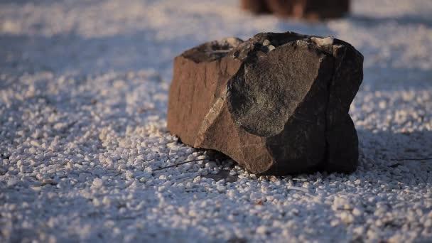 Velký černý kámen ležící na malé bílé oblázky