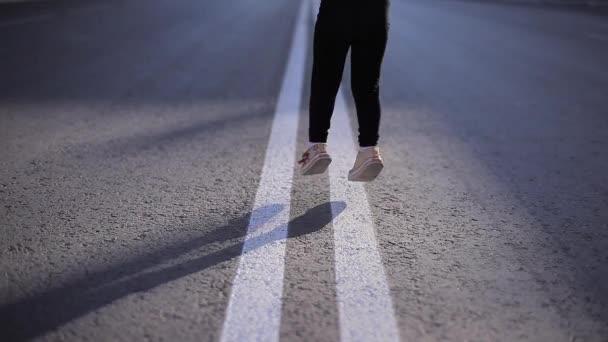 Malá holčička v černém obleku s bílé ponožky a boty dělá Fitness a jógy sedí na dálnici na dvojité souvislý pás pod sluncem a větrem