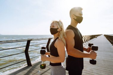 Young couple in protective masks  doing sports exercises at the beach pier. Athlete man and sportive woman jogging together on the quay near the sea.Sport, Active life. Covid-19.