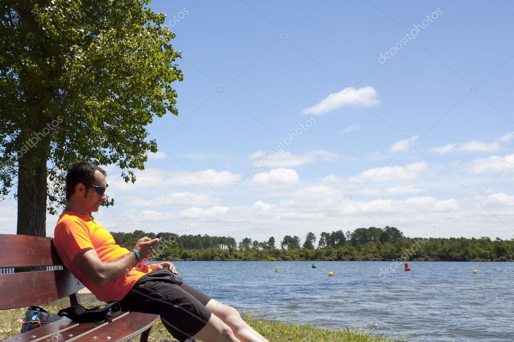 guy sending a message in his mobile sit in a bench close to the lake