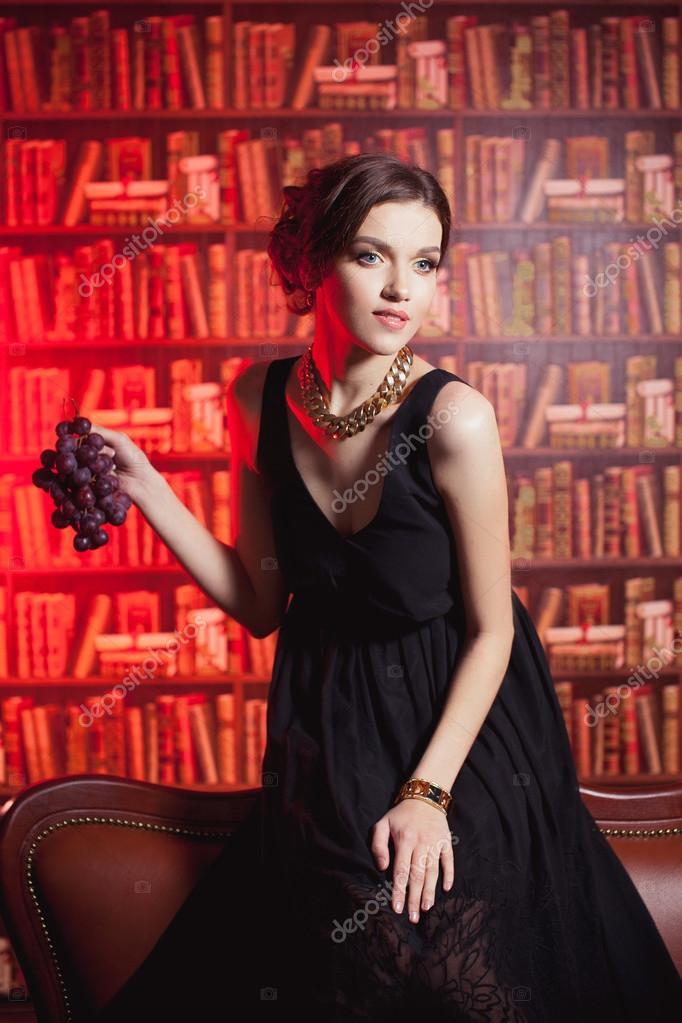 cc4db652d41a Bella ragazza in un vestito nero su una priorità bassa della libreria con un  melograno in mano su un divano marrone — Foto di Tatyaby2016.gmail.ru