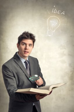 Young businessman looking at a book with magnifying glass
