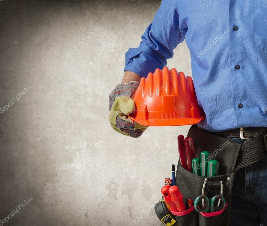 Worker in uniform holding tools
