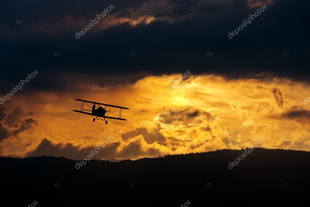 Biplane in evening sky