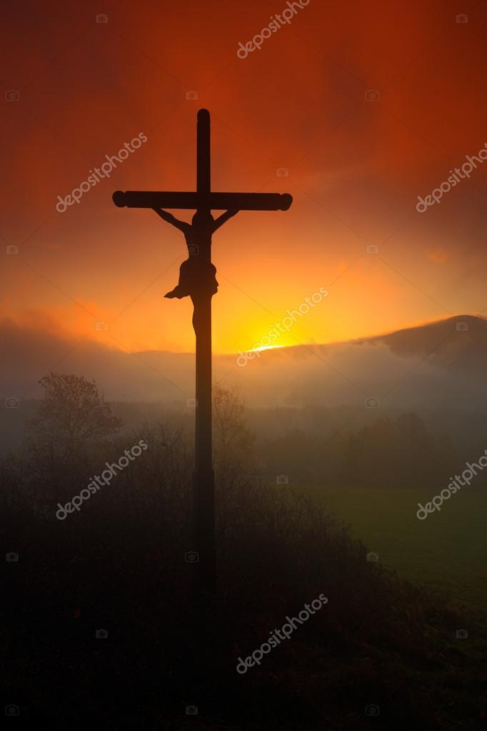Cross and beautiful sunset with fog