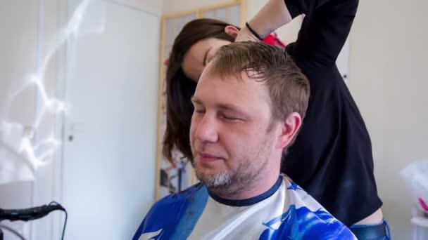 Closeup kadeřník holič žena ruce s nůžkami nakrájíme krátké zákazník muže chloupky v kadeřnický salon