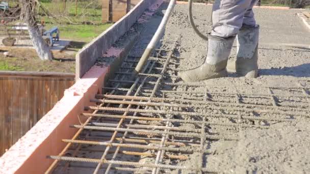 Pracovník léčených tekutý beton vibrátor v bednění s imitací