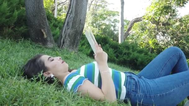 Mladá dívka ležící na trávě a čtení knihy.