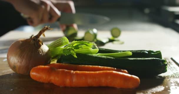 ein erfahrener Koch arbeitet mit Zutaten in der Küche in extremer Zeitlupe Zucchini und Karotten und Zwiebeln