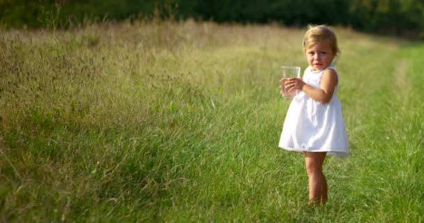 beautiful little girl about two years immersed in nature , dressed clean try to make