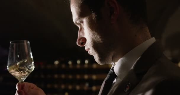 Slow motion of young sommelier dressed in formal jacket and tie smells and tries white wine poured in transparent glass in a dark wine cellar 4k (close up)
