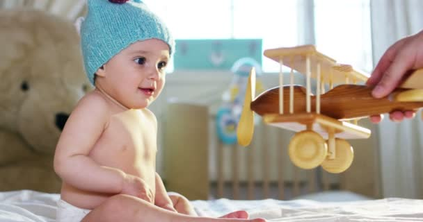A cute little baby is looking into the camera and is wearing a light blue hat, his dad play with a wood toy aeroplane