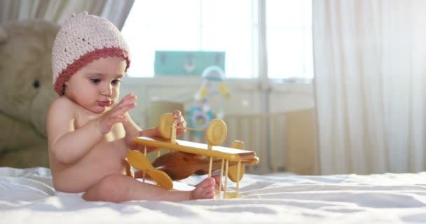 Sladké dítě se dívá do kamery a je růžový klobouk, dítě kolem sebe a hrát si s dřevěnou hračkou letadla
