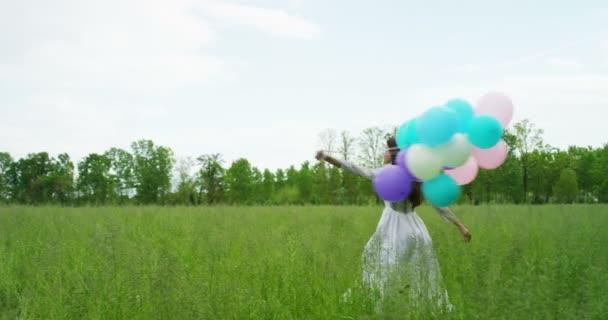 Žena s balónky v louce