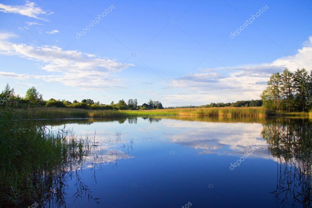 Fishing rod in hand on a background of lake
