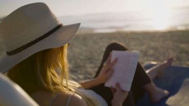 Krásná žena, sedí a čtení na pláži