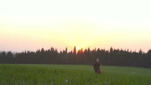 Chlapec s superman mys v poli při západu slunce