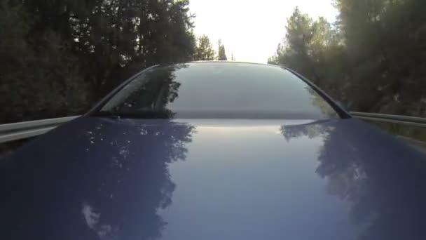 Modré auto ve vysoké rychlosti přes silnici krajiny