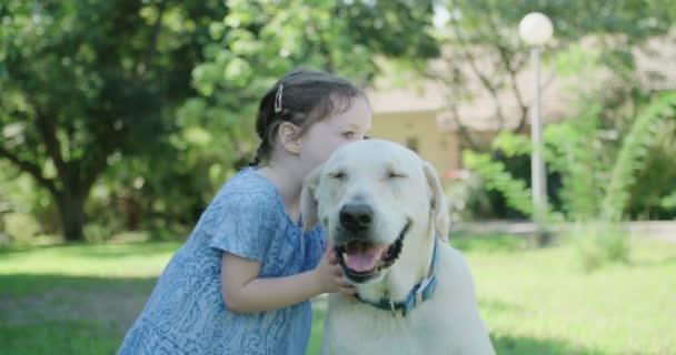 Little girl kissing a big white dog