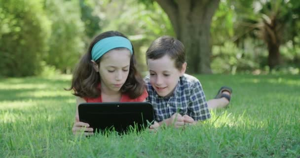 A boy and a girl laying on the lawn playing with a tablet computer