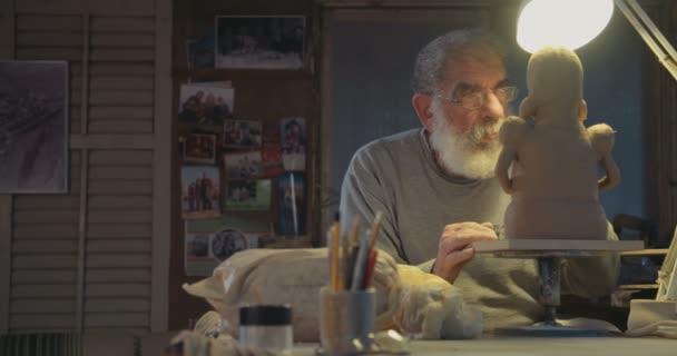 Starý umělec modely hliněné plastiky v malé studio