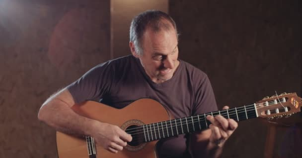 Musician playing acoustic guitar in a recording studio