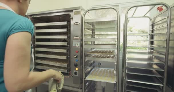 Baker taking cookies out of the oven at a bakery