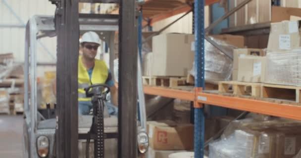Logisztikai munkavállaló egy targonca vezetői egy raktárban, és majd ellenőrzésére az elemeket a vágólap segítségével
